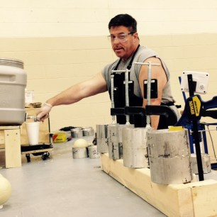 Apex Sports founder, William Wilson, works with machinery he created in his factory at the Muskingum County Business Incubator in order to create his one-of-a-kind softballs