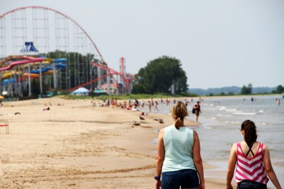 Guests take a break from the amusement park by relaxing on the sandy shores of Cedar Point Beach.
