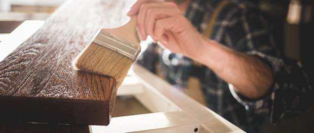 Close up of paintbrush applies paint or varnish on wooden board in carpentry worksho