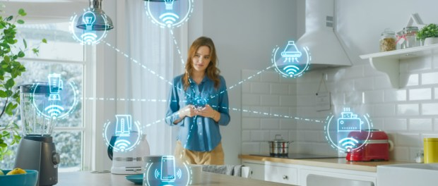 Woman standing in kitchen with smart device connections around her
