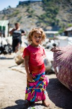 A Roma girl inspects me from her families encampment filled with things they had collected.