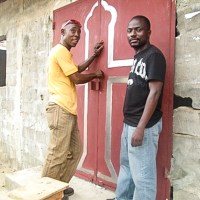 church leaders in Liberia stand next to a new door on a church building