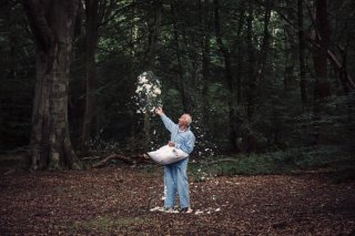 A man throwing pillow feathers into the air.
