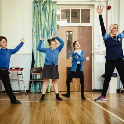 Three primary school pupils and a woman with their arms in the air.