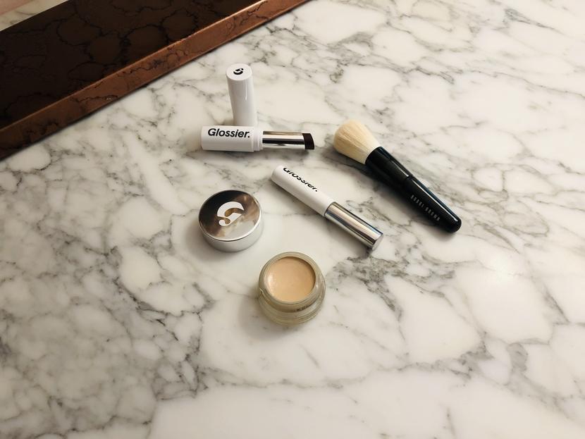 Flatlay with Glossier Stretch Concealer, Boy Brow, Generation G Lipstick & Bobbi Brown mini face brush