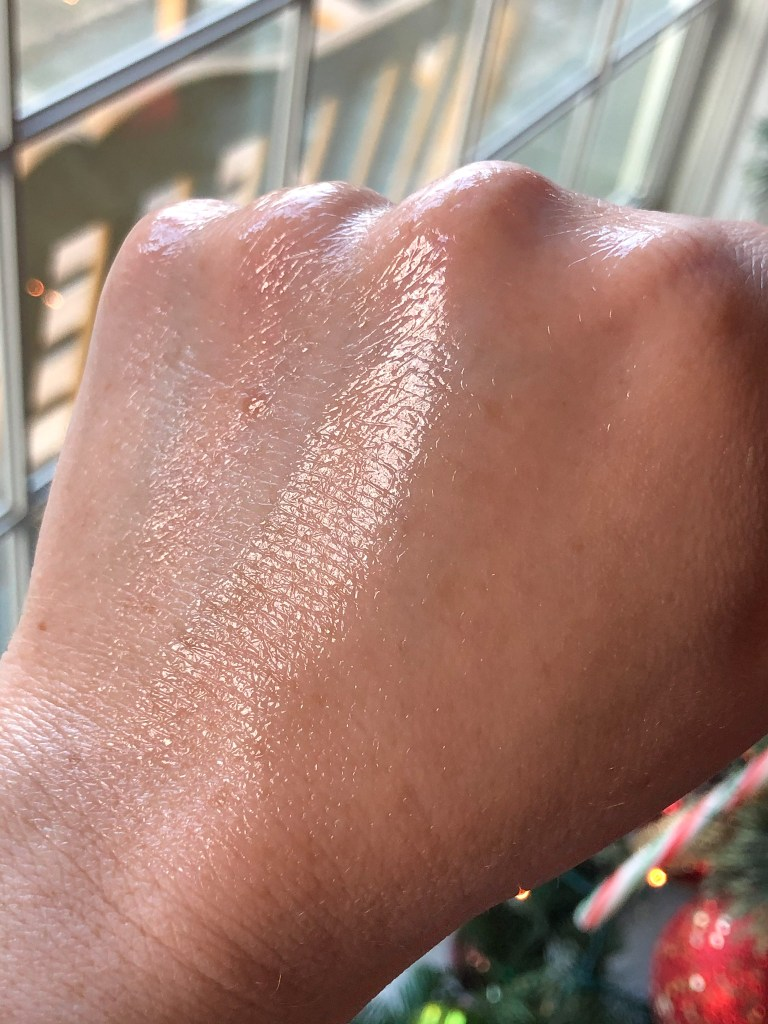 Glossier Futuredew blended on the back of my hand to show the glossy finish