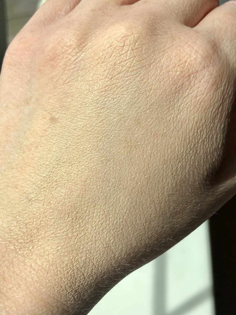 The Fenty Beauty Eaze Drop Blurring Skin Tint in the shade 2 blended into the back of my hand