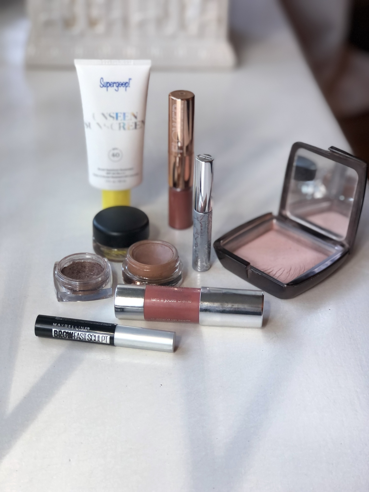 Some of my favorite products from my collection, including brow gel, blush, eyeshadow, primer, SPF, powder, mascara & lipstick