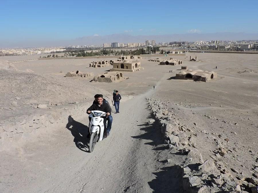 Ragazzi che salgono con un motorino la salita di una delle torri del silenzio Dakhmeh-ye Zartoshtiyun