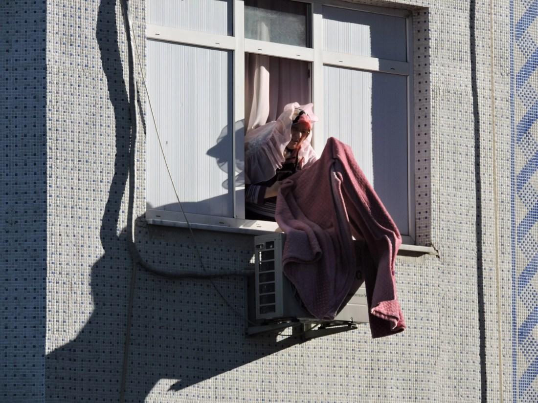 Una signora raccoglie i panni, facendo attenzione a non scoprire il capo, nel quartiere di Fener a Istanbul
