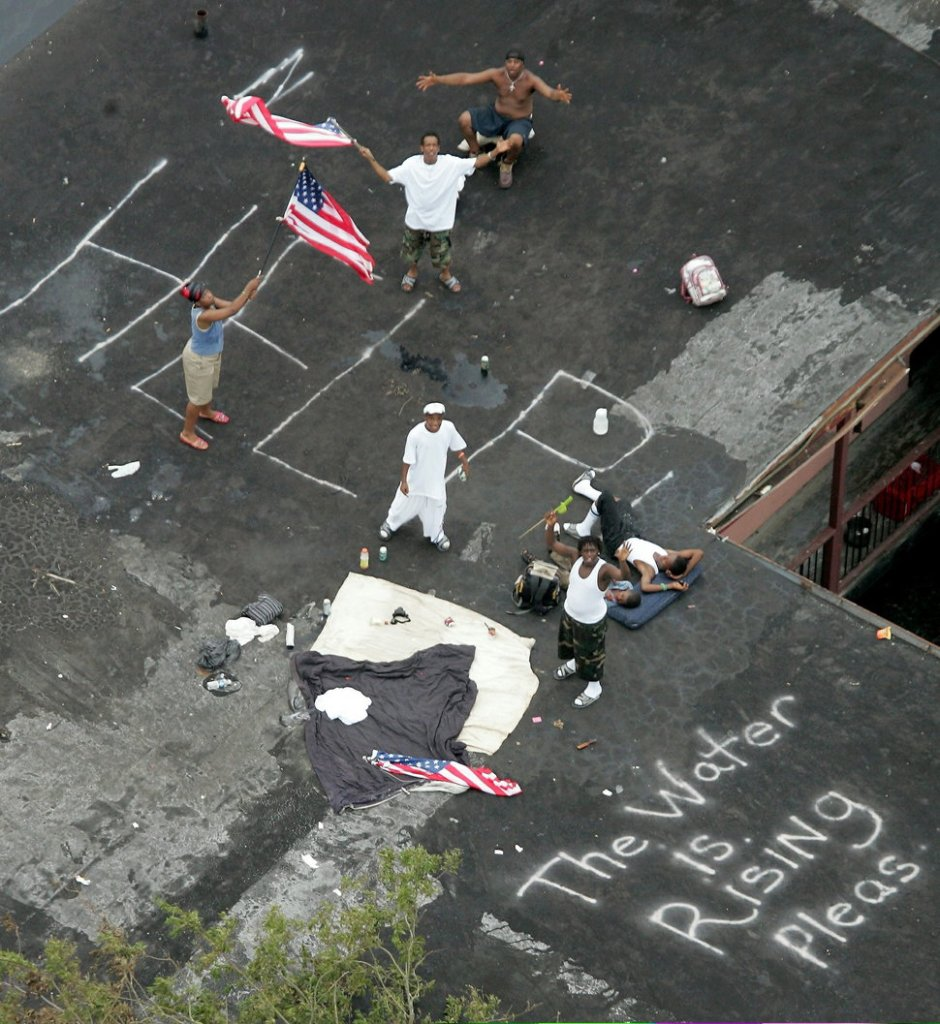 01 Sep 2005, New Orleans, Louisiana, USA --- Residents wait to be rescued from the floodwaters of Hurricane Katrina in New Orleans September 1, 2005. Chaos and lawlessness hampered the evacuation of New Orleans on Thursday and a U.S. senator said thousands may have died in Louisiana after Hurricane Katrina devastated the U.S. Gulf Coast. In New Orleans, shell-shocked officials tried to regain control of the historic jazz city reduced to a swampy ruin by Monday's storm. Bodies floated in the flooded city and authorities still could only guess how many people had died. --- Image by © David J. Phillip/Pool/Reuters/Corbis