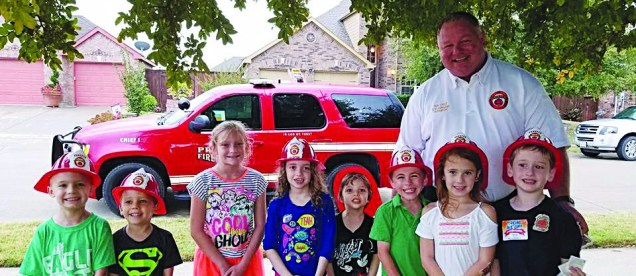 Chief Stuart Blasingame poses with some neighborhood kids at the National Night Out Block Party on Tuesday, October 3rd.