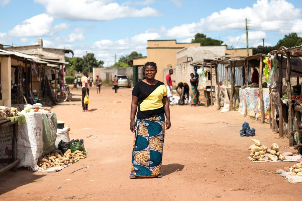 Mwila stands in the middle of the market where she runs her business.