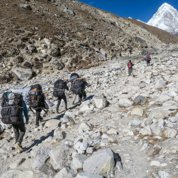 Nepali Sherpas climbing a mountain in Nepal with heavy load on their backs