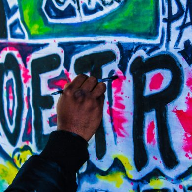 """A graffiti artists painting the word """"poetry"""" on a wall"""