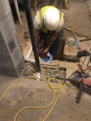Plumber cutting pipe to run to water fountain.