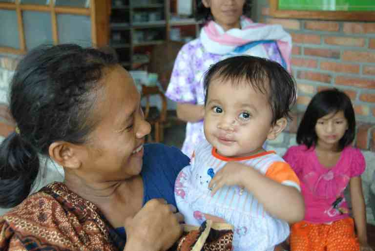 Smiling lady with Sumatran infant