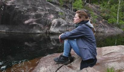 Yalou op een rots bij het water in Zweeds Lapland