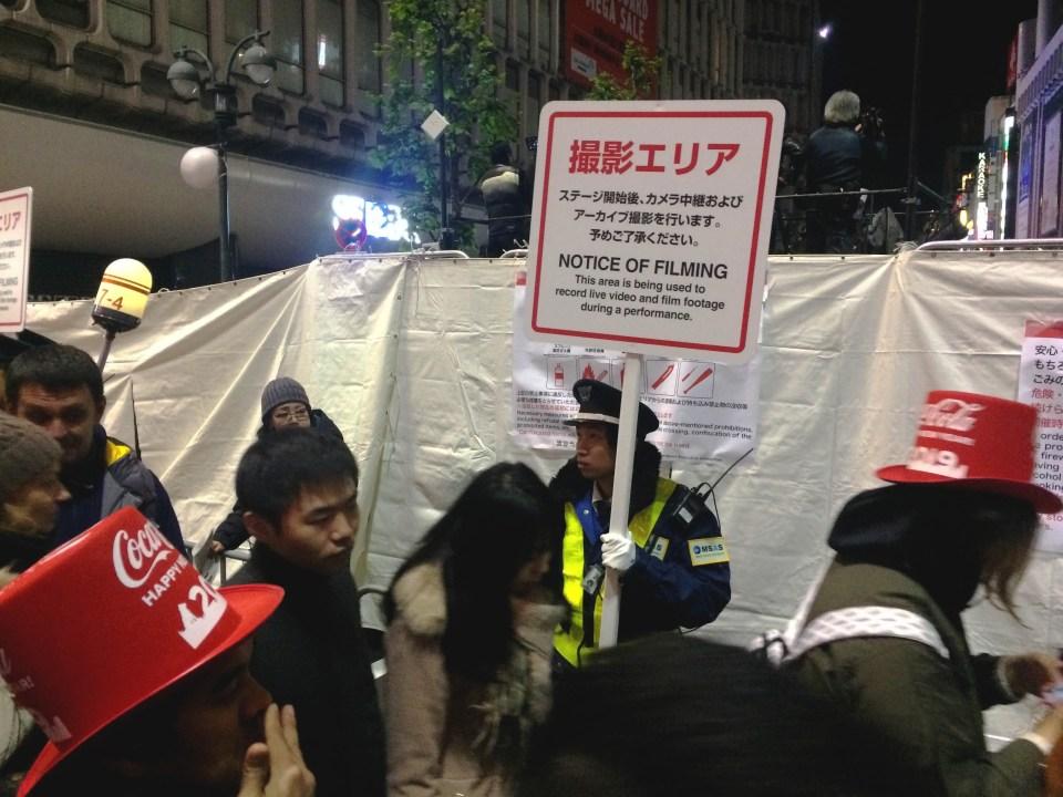 Japanse politie met een bord dat er gefilmd wordt