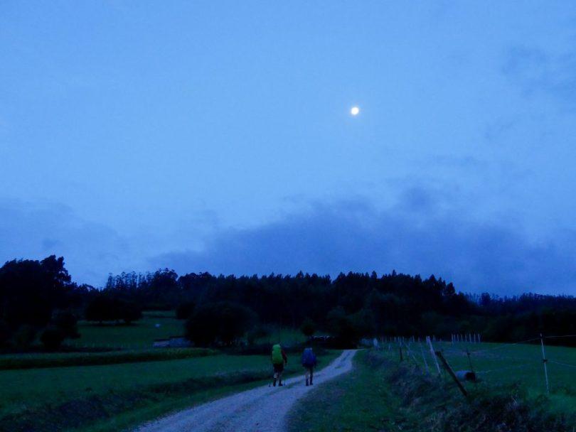 Twee pelgrims lopen op een door de maan verlicht pad
