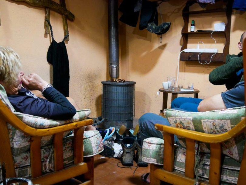 Schoenen staat te drogen voor een kachel waarop kastanjes liggen te roosteren