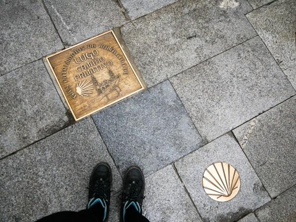 Het logo van de Camino Primito op de vloer met mijn voeten erbij in beeld