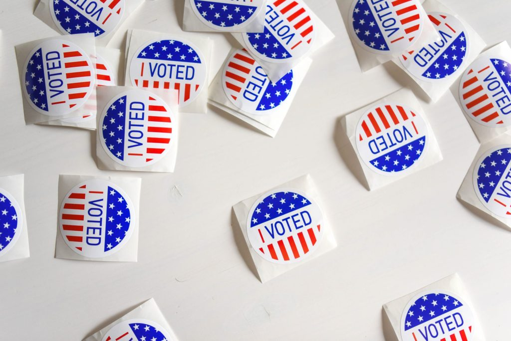 """Numerous """"I voted"""" stickers strewn across a white surface."""