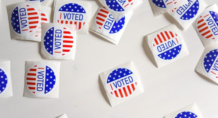 "Numerous ""I voted"" stickers strewn across a white surface."