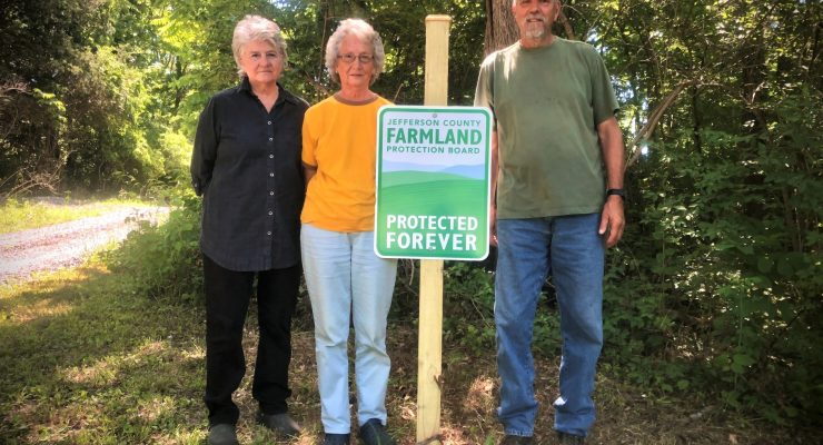 The Ware Family standing outside next to a sign that declares their farmland has been authorized for a conservation easement.