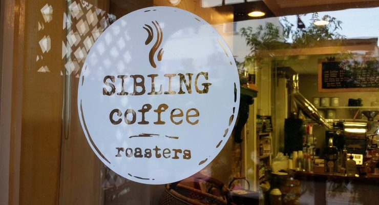 Logo for Sibling Coffee in Charles Town printed as a decal on the stores glass window.