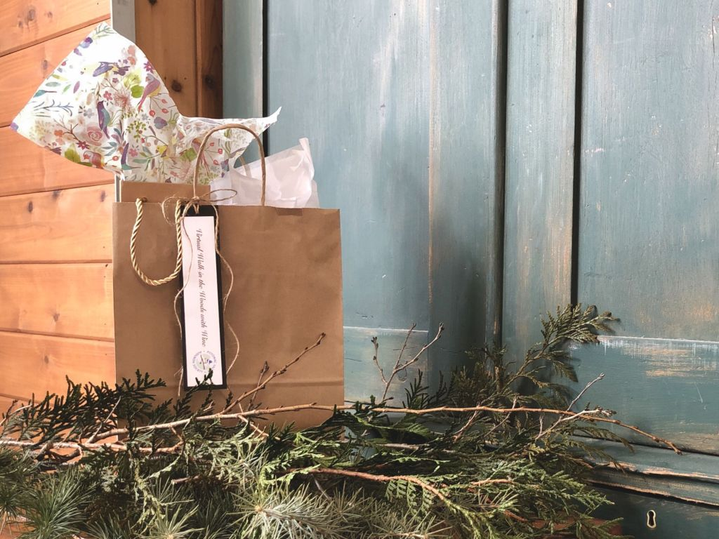 A decorative brown paper gift bag containing a bottle of wine.