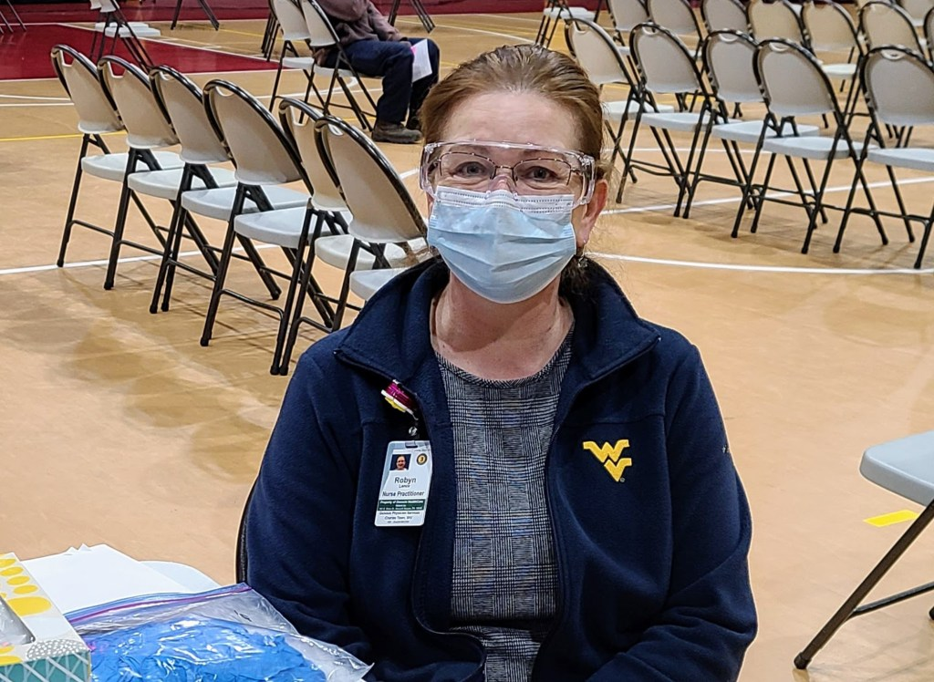Robyn Lance, a nurse practitioner, seated behind a folding table at a covid-19 vaccination clinic.