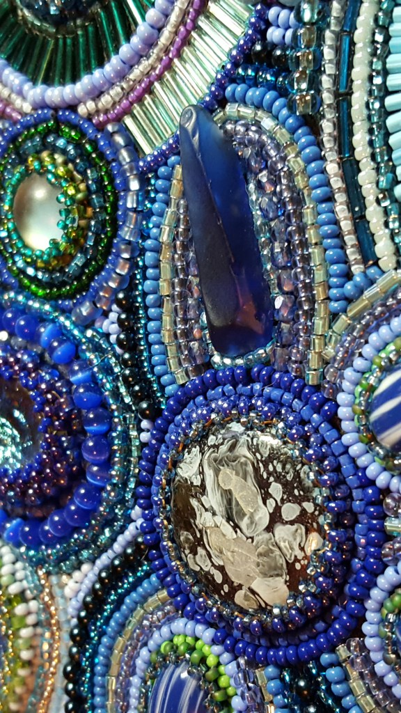 A detailed view of a stone and beads collage by Lisa Ashton.