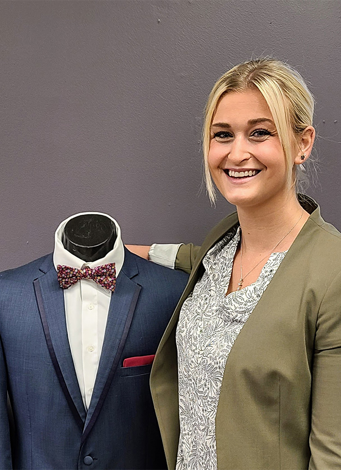 elissa Grant of Cape Cod Formals stands next to a suit-clad mannequin.