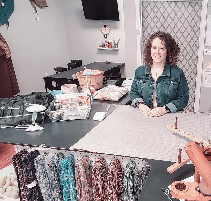 Karen Frail of Yarnability sits amongst her wares.