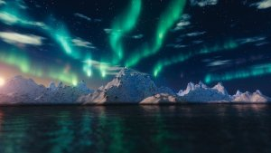 Northern lights above an ocean with Icebergs