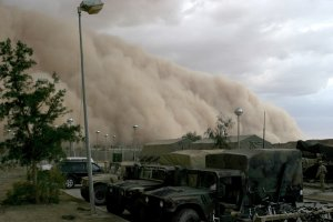 Dust storm with military vehicles in the foreground
