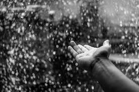 A photo of a hand reaching out in the rain
