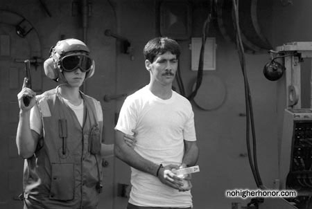 An armed sailor aboard the amphibious transport dock USS Raleigh (LPD 1) escorts an Iranian detainee from the Iran Ajr during Operation Prime Chance, a part of the U.S. Navy's Operation Earnest Will.