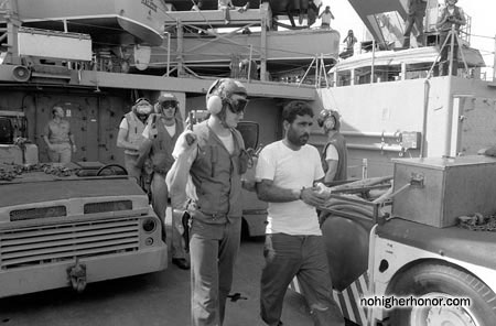 An armed sailor aboard the amphibious transport dock USS Raleigh (LPD 1) escorts an Iranian detainee from the Iran Ajr, which was captured during Operation Prime Chance, a part of the U.S. Navy's Operation Earnest Will.