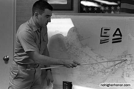 Lt. Dana Wiener, intelligence officer aboard the U.S. Navy guided missile frigate USS Nicholas (FFG 47), indicates the positions of ships in the Strait of Hormuz during a 1 June 1988 intelligence briefing during Operation Earnest Will.