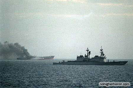 During Operation Earnest Will, the U.S. Navy destroyer USS CHANDLER (DD 996) passes by the burning Greek tanker ARIANDE as fire tugs attempt to put out the blaze. The tanker was attacked earlier by small gunboats.
