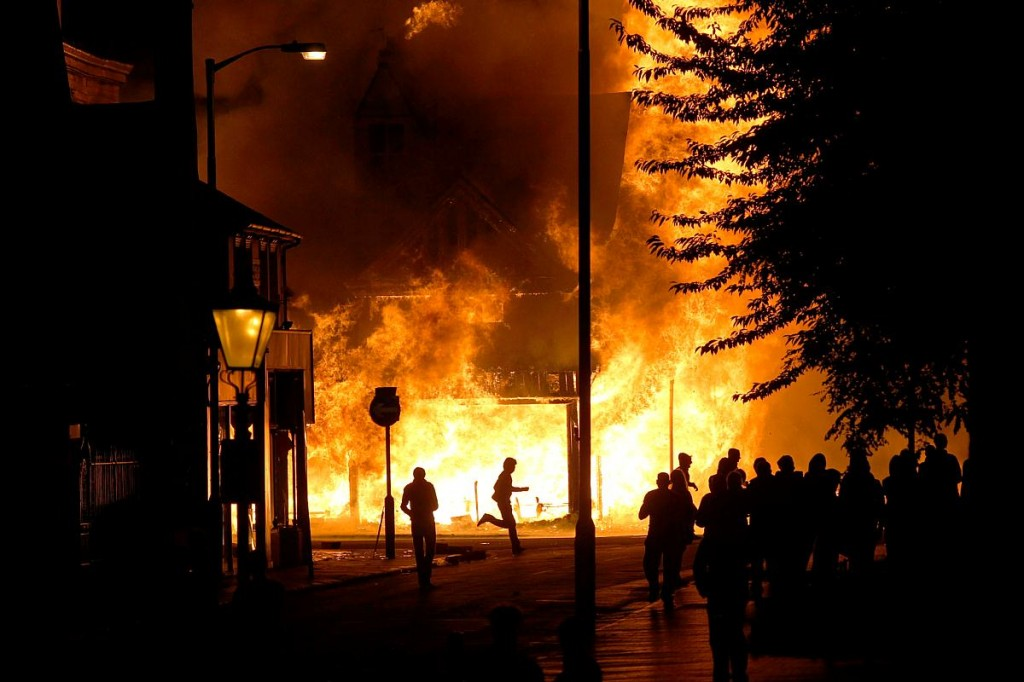 London riots, people in streets with burning cars and buildings in background.