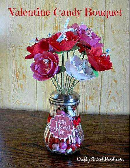 A cute Valentine Candy Bouquet of Hershey Kiss Roses in a vase filled with red and pink M&M's. Makes a great #valentinesday gift for grandparents or teachers! via CraftyStateofMind.com