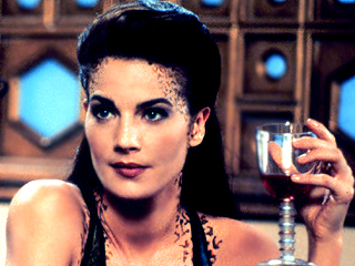 Jadzia Dax, a character from Star Trek: Deep Space Nine. She resembles a white woman with dark reticulations in two stripes that run along her hairline, neck, and collarbones.