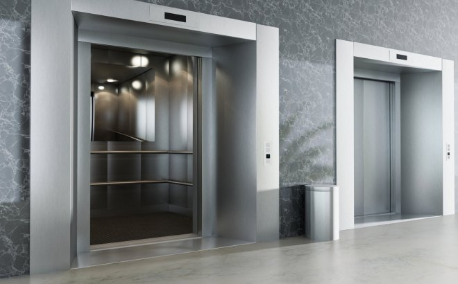 A shiny metal elevator in the lobby of a large building.
