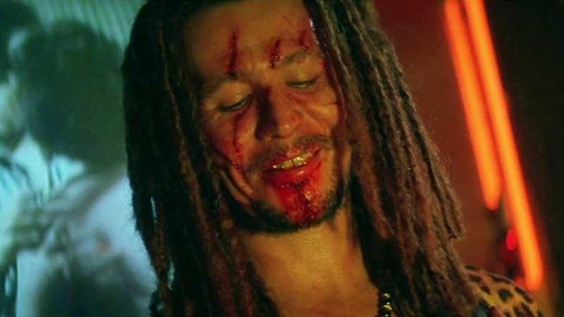 Gary Oldman as Drexl in True Romance with scratches on his face, grinning