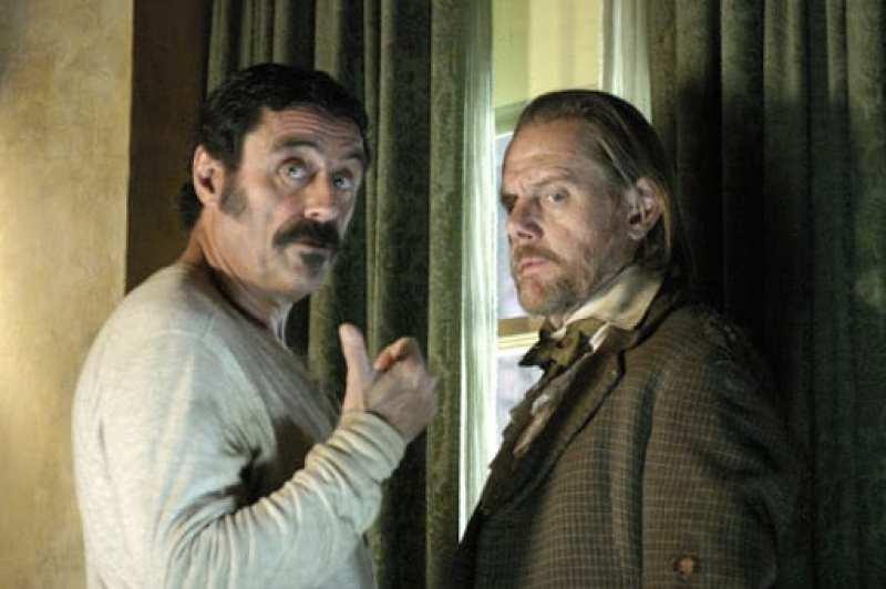 Swearengen and EB Farnum talk standing by a window