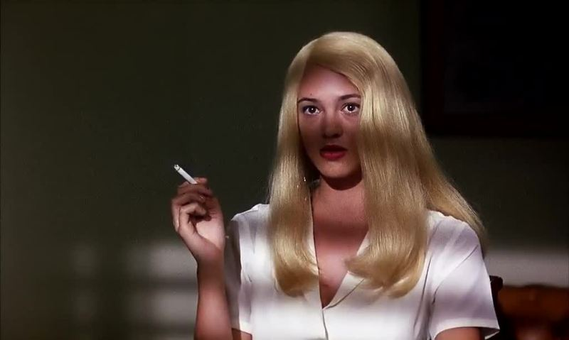 Anna wears a blonde wig and smokes a cigarette