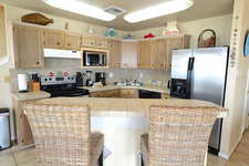 Fully equipped kitchen open to dining and living areas with snack bar.